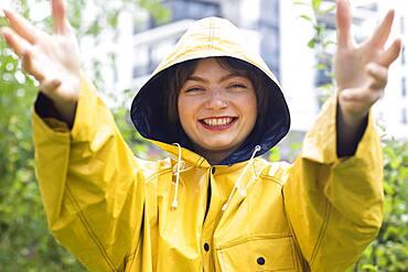 Happy young woman with yellow rain jacket with hood, Baden-Wuerttemberg, Germany, Europe