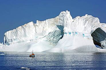 Small fishing boat in front of huge iceberg with two holes, Disko Bay, Ilulissat, Greenland, Denmark, North America