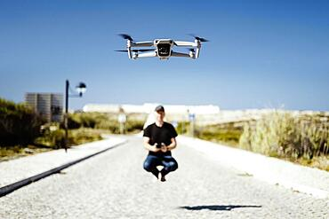 Man holding remote flying together with his drone in first plan