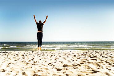 Man jumping on the beach with hands up