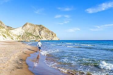 Young man walking on a beach, sandy beach with rocky cliffs, Paralia Paradisos, Kos, Dodecanese, Greece, Europe