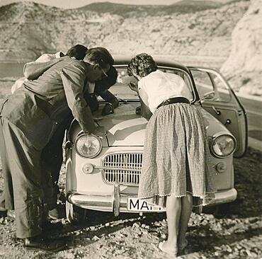 Former People's Republic of Yugoslavia in 1959: young German tourists on a coastal road i, studying a map spread out on the bonnet of their car, Croatia, Europe