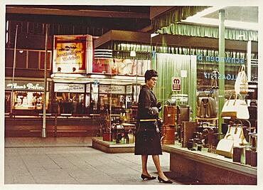 Stuttgart at night in 1963: A young woman with a coat and handbag looks at the display of handbags and suitcases in a leather goods shop, in the back a cinema with the announcement of the film Ein fast anstaendiges Maedchen starring Liselotte Pulver, Baden-Wuerttemberg, Germany, Europe