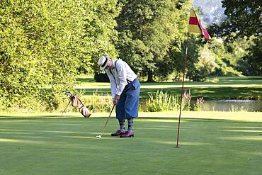 Older man in straw hat and knickerbockers playing hickory golf on a golf course