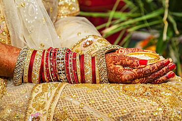 Traditional bridal jewelry and henna decoration on the hands of the bride during a religious ceremony at a Hindu wedding, Mauritius, Africa