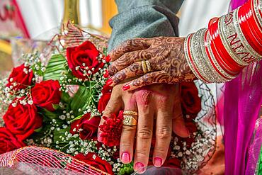 Hands of newly married couple with their wedding rings and bridal Bouquet, Mauritius, Africa