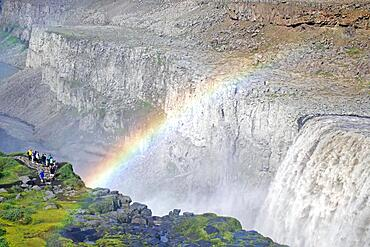 Rainbow in front of waterfall, people on the left, stone desert in the background, Dettifoss, Joekulsa a Fjoellum, Iceland, Europe