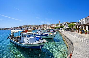 Fishing boats in the harbour of Halki with turquoise water, promenade with colourful houses of the village of Halki, Halki, Dodecanese, Greece, Europe
