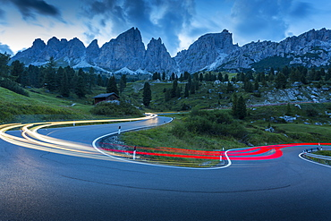 Car trail lights on Passo Pordoi with mountain backdrop at dusk, Province of Bolzano, South Tyrol, Italian Dolomites, Italy, Europe