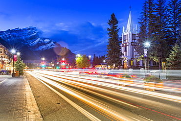 Trail lights on Banff Avenue and St. Paul's Presbyterian Church, Snow Peak visible through clouds, Banff, Banff National Park, Alberta, Canada, North America