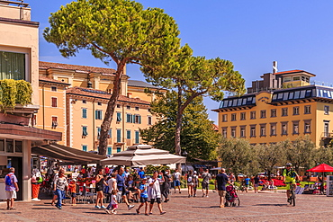 View of restaurants and pastel coloured architecture in Piazza Garibaldi, Riva del Garda, Lake Garda, Trentino, Italian Lakes, Italy, Europe