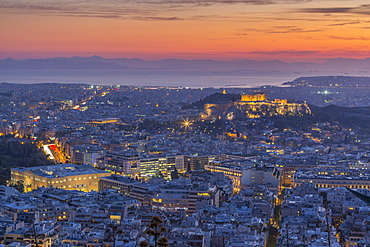 View of Athens and The Acropolis from Likavitos Hill and Aegean Sea visible on horizon at sunset, Athens, Greece, Europe