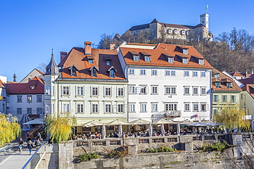 View of buildings along Ljubljanica River and Castle visible in background, Ljubljana, Slovenia, Europe