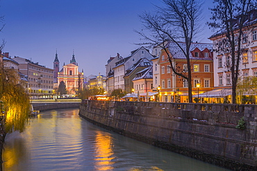 Ornate facade of Franciscan Church of the Annunciation and Ljubljanica River at dusk, Ljubljana, Slovenia, Europe