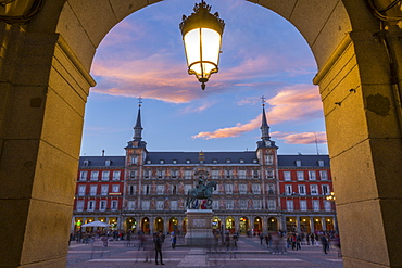 View of Casa de la Panaderia in Plaza Mayor through archway at dusk, Madrid, Spain, Europe