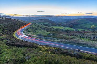 Light trails on road through Peak District National Park, England, Europe