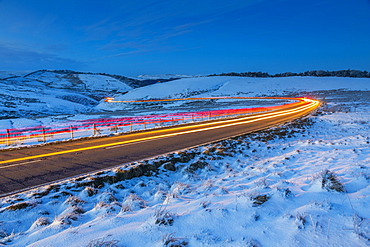 View of trail lights on frozen landscape near Buxton at dusk, High Peak, Derbyshire, England, United Kingdom, Europe