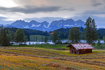 View of traditional log cabin and Kaiser Mountain Range backdrop at Schwarzsee near Kitzbuhel, Tyrol, Austria, Europe