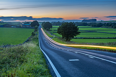 View of trail lights on the A515 near Newhaven at dusk, Peak District National Park, Derbyshire, England, United Kingdom, Europe