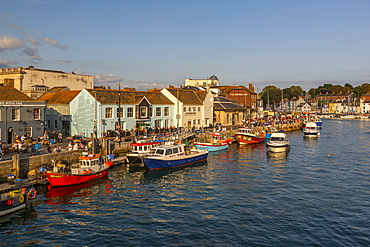 View of boats in the Old Harbour and quayside houses at sunset, Weymouth, Dorset, England, United Kingdom, Europe