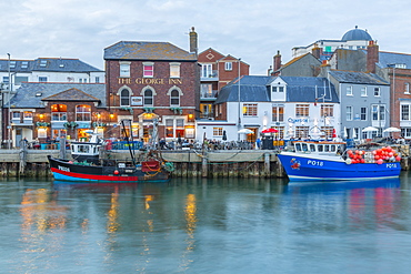 View of boats in the Old Harbour and quayside houses at dusk, Weymouth, Dorset, England, United Kingdom, Europe