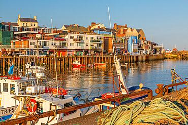 View of harbour boats and harbourside shops in Bridlington Harbour at sunset, Bridlington, East Yorkshire, England, United Kingdom, Europe
