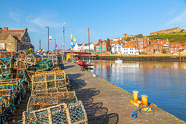View of St. Mary's Church and fishing baskets, houses and boat on the River Esk, Whitby, Yorkshire, England, United Kingdom, Europe