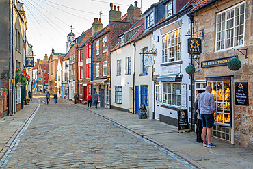 View of shops on traditional cobbled street in historic town centre, Whitby, Yorkshire, England, United Kingdom, Europe