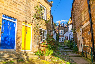 View of houses in The Opening and narrow cobbled alley in Old Bay, Robin Hood's Bay, North Yorkshire, England, United Kingdom, Europe
