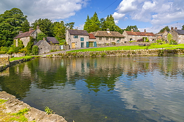 View of cottages reflecting in village pond, Tissington, Peak District National Park, Derbyshire, England, United Kingdom, Europe