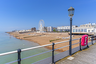 View of beach front houses and ferris wheel from the pier, Worthing, Sussex, England, United Kingdom, Europe