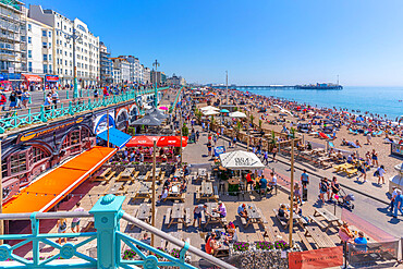 View of beach, sea front cafe and Brighton Palace Pier on a sunny day, Brighton, East Sussex, England, United Kingdom, Europe