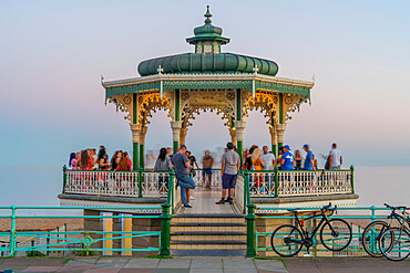 View of people on ornate bandstand on sea front at dusk, Brighton, East Sussex, England, United Kingdom, Europe