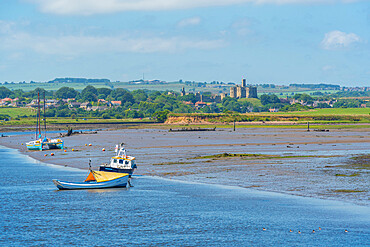 View of Warkworth Castle and boats on River Coquet from Amble, Morpeth, Northumberland, England, United Kingdom. Europe