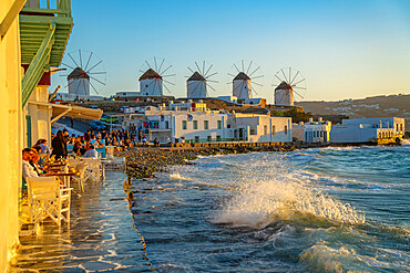 View of the windmills and crashing waves in Mykonos Town at sunset, Mykonos, Cyclades Islands, Greek Islands, Aegean Sea, Greece, Europe