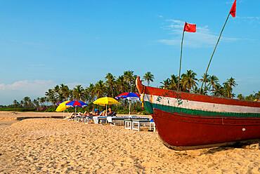 Traditional fishing boat and sunbathers on beach, Benaulim, Goa, India, Asia