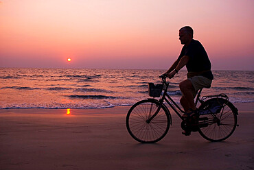 Sunset and cyclist, Goa, India, Asia