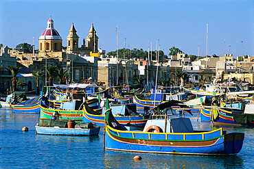 View across harbour with traditional Luzzu fishing boats, Marsaxlokk, Malta, Mediterranean, Europe