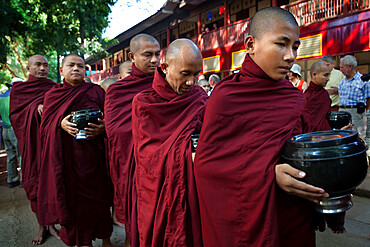 Buddhist monks lining up to receive donations of rice for lunch, Mahar Gandar Yone Monastery, Mandalay, Myanmar (Burma), Asia
