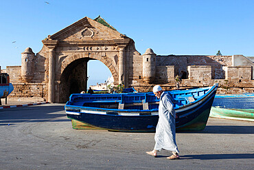 Old Muslim man walking below the old city gate and ramparts, Essaouira, Atlantic coast, Morocco, North Africa, Africa