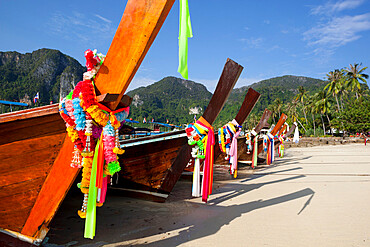 Garlands decorating long-tail boats on beach, Koh Phi Phi, Krabi Province, Thailand, Southeast Asia
