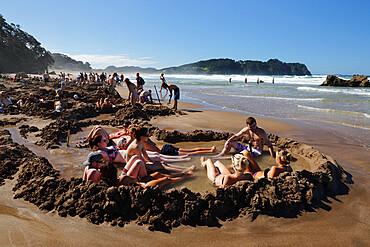 Tourists relaxing in hot pools dug on beach, Hot Water Beach, Coromandel Peninsula, Waikato, North Island, New Zealand, Pacific
