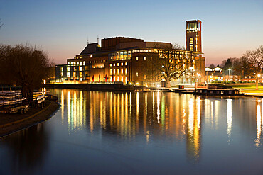 Royal Shakespeare Theatre lit up at dusk beside River Avon, Stratford-upon-Avon, Warwickshire, England, United Kingdom, Europe