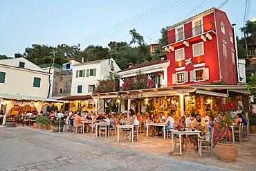 Harbourside restaurants in evening, Loggos, Paxos, Ionian Islands, Greek Islands, Greece, Europe
