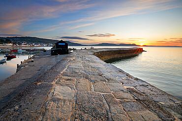 The Cobb with the cliffs of Jurassic Coast at sunrise, Lyme Regis, Dorset, England, United Kingdom, Europe