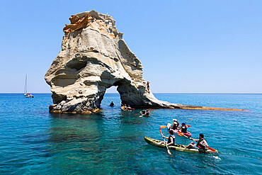 Kayakers go through arch rock formation with crystal clear water, Kleftiko, Milos, Cyclades, Aegean Sea, Greek Islands, Greece, Europe