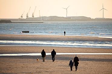 Walkers on the beach at sunset with docks of Boulogne-sur-Mer behind, Wimereux, Pas-de-Calais, Hauts-de-France region, France, Europe