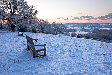 Bench overlooking snow covered High Weald landscape at sunrise, Burwash, East Sussex, England, United Kingdom, Europe