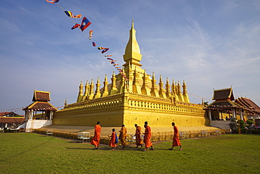 The golden Buddhist stupa of Pha That Luang with Buddhist monks walking below, Vientiane, Laos, Indochina, Southeast Asia, Asia