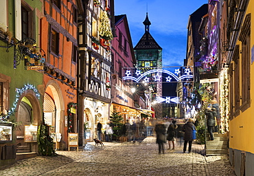 Rue du General de Gaulle covered in Christmas decorations illuminated at night, Riquewihr, Alsace, France, Europe